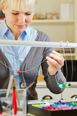 Frau bei Herstellung einer Halskette