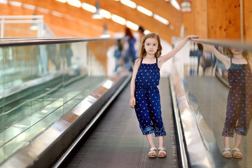 Cute child in shopping center on moving staircase