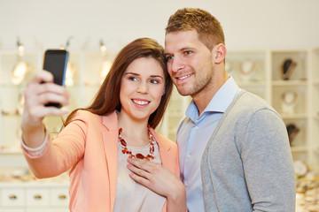 Paar macht Foto mit Smartphone beim Juwelier