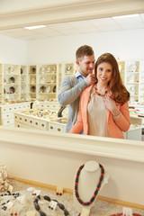 Frau probiert Halskette vor Spiegel an