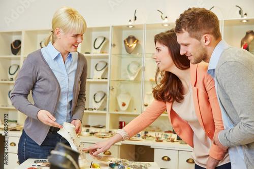 Verkäufer redet mit Paar im Schmuckladen - 66296392