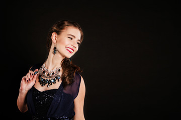 party happy woman with perfect makeup wearing jewelry on black