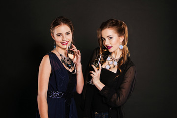 Cheerful young beauties with flutes of champagne having a