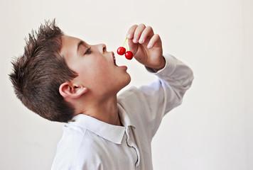Nino con la boca abierta,comiendo cerezas