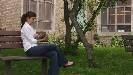 caucasian woman on a bench in a park with tablet