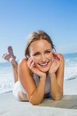 Fit smiling woman lying on the beach