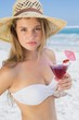 Pretty blonde holding cocktail on the beach