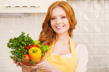 portrair of smiling young woman in the kitchen with salad