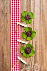 Holzhintergrund mit Geschenkband und vierblättrigen Kleeblättern