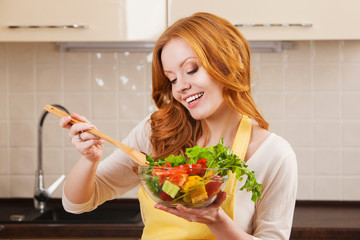 Smiling young woman in the kitchen with healthy food