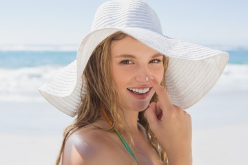 Beautiful girl putting spf on nose on the beach smiling at camer