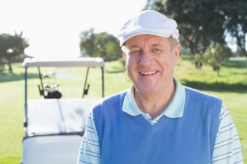 Happy golfer smiling at camera with golf buggy behind