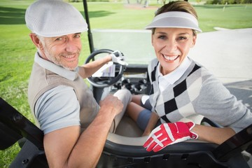 Golfing couple smiling at camera in their golf buggy