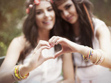 Boho girls showing heart shape from hands poster