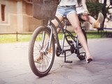 Part of boho girls legs during riding tandem bike poster