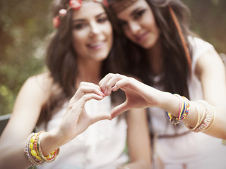 Boho girls showing heart shape from hands