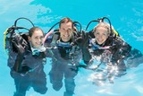 Smiling friends on scuba training in swimming pool looking at ca