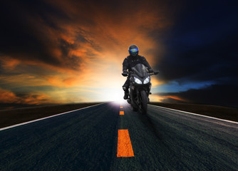 young man riding motorcycle on asphalt road
