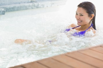 Smiling brunette in bikini relaxing in hot tub