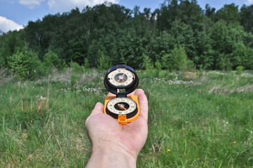 Compass in hand, against background of the forest.