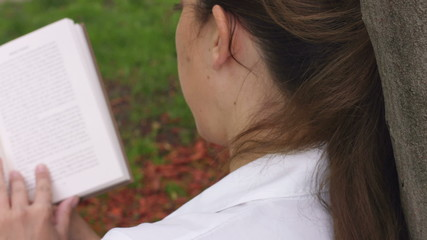 caucasian woman sitting in the grass park reading book