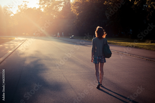canvas print picture Woman walking into sunset in a park