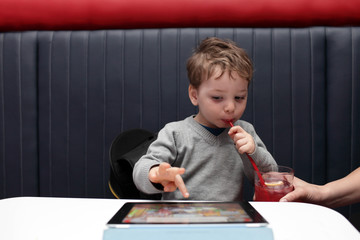 Child drinking juice and playing on PC