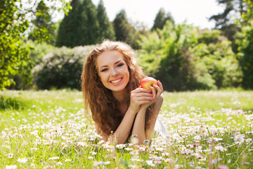Charming girl with red apple laying on green grass