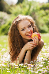 young smiling beautiful woman with apple laying on green grass
