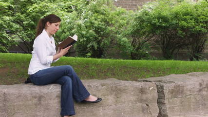caucasian woman in a park reading book