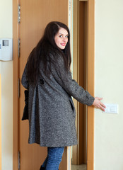 Woman in coat   leaving the home