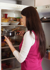 woman looking in to pan from  fridge