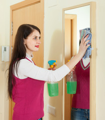 woman cleaning  mirror  with cleanser