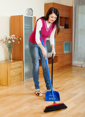 Brunette  woman sweeping the floor