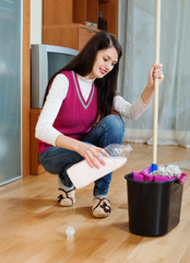 brunette girl washing  floor with detergent