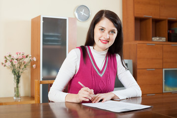 Smiling brunette woman staring financial documents