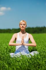 Beautiful young woman doing yoga exercise on field. Yoga