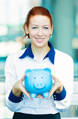Portrait business woman holding piggy bank in corporate office