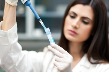 Female researcher filling a test tube