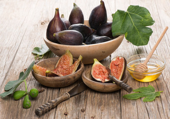 Ripe figs in a bowls and honey over rustic  wooden table