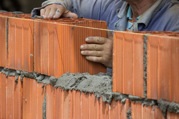 Builder worker installing clay block wall, lay clay block