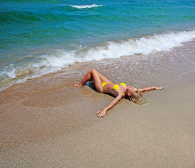 beautiful slender young blonde woman lying on the sea beach