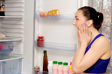 Girl in horror at the open refrigerator