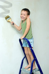 A boy stands on a ladder and paints the wall