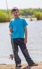 boy with a fishing rod on the river bank