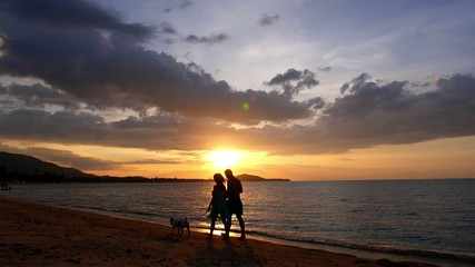 Couple with Cute Dog Walking on the Beach against Sunset.