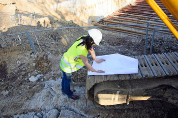 Young female architect at the construction site of the construct