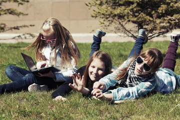 Teenage school girls lying on the grass in campus