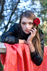 passionate look of attractive girl with red rose in her hair