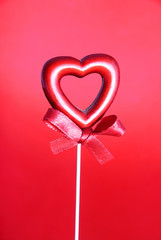 red valentine heart with bow against red background